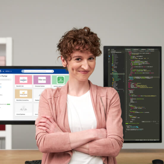 Coder standing with arms crossed at her desk with two monitors behind her. One with the Partner Portal interface, the other with PHP web code.