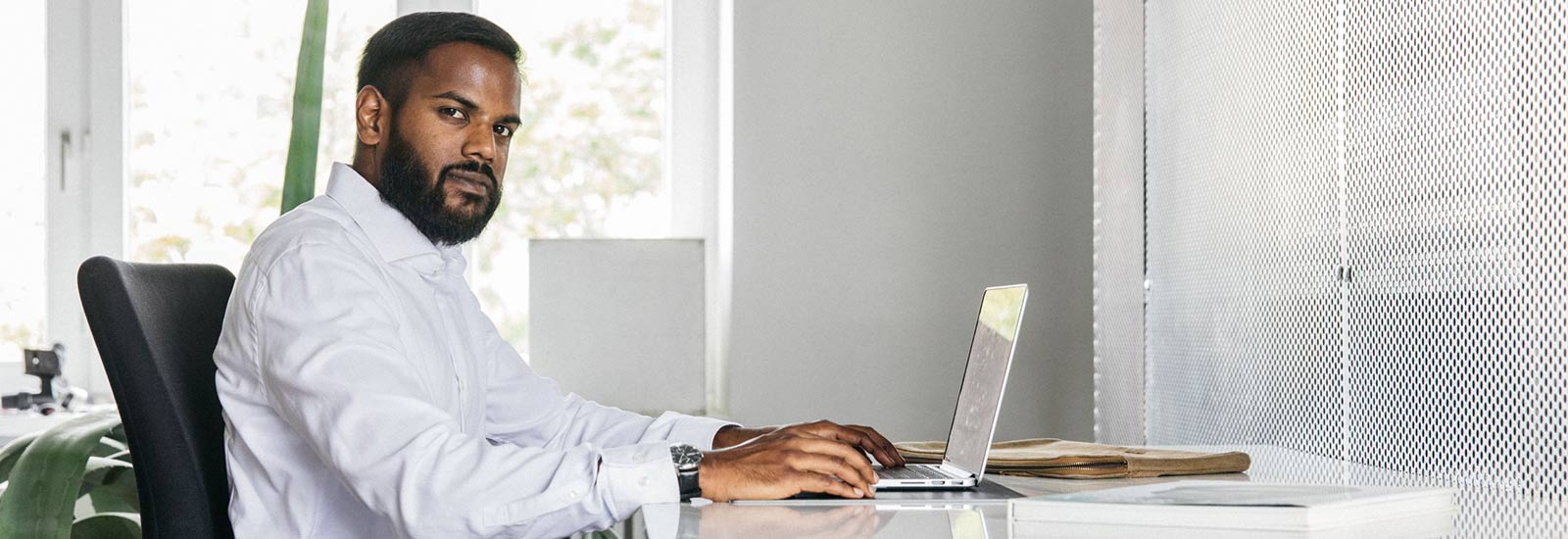 Man sitting in front of a laptop in his office