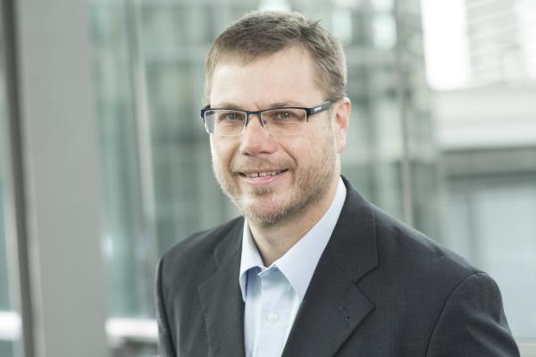 Foto de perfil; hombre con gafas, camisa azul claro y chaqueta negra