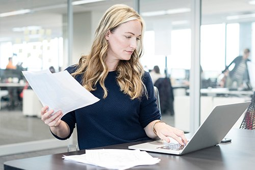 Blonde office woman working at her laptop with a piece of paper in her other hand