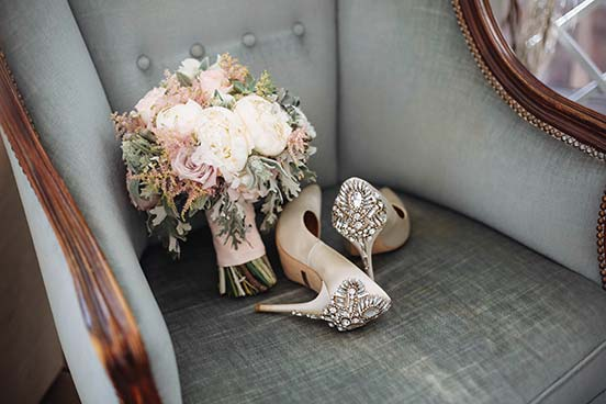 Bridal bouquet and bridal shoes on grey armchair