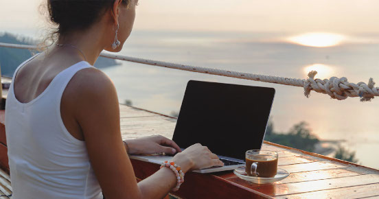 Woman on laptop with a mediterranean backdrop