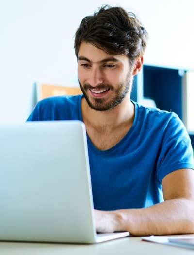 Man smiling while working on his laptop