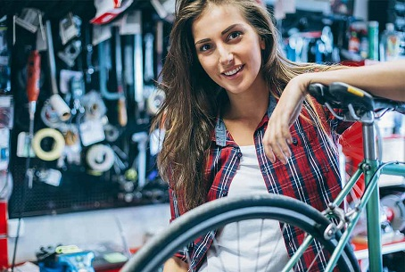 Woman in a bicycle workshop leaning on a bike