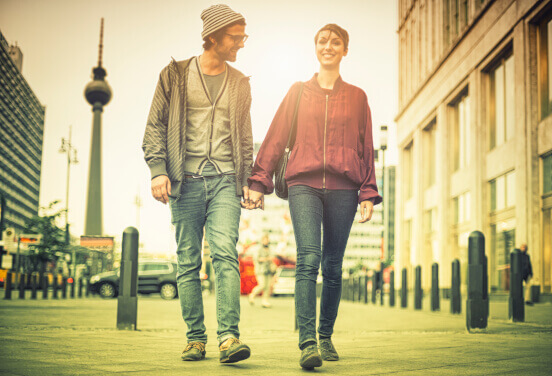 Couple holding hands while walking down a city street