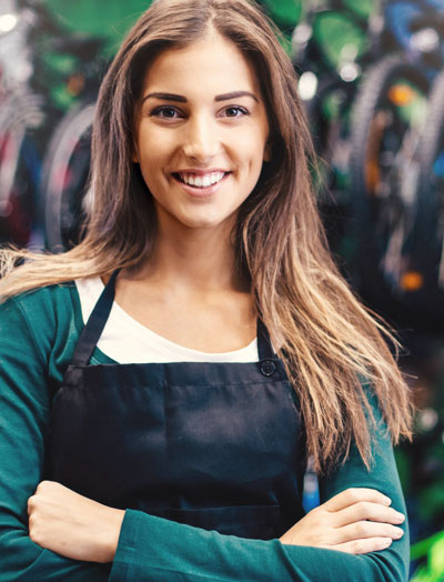 Smiling woman wearing an apron crossing her arms; MyWebsite customer testimonial