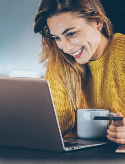 Mujer sosteniendo una taza de café y sentada frente a un cuaderno