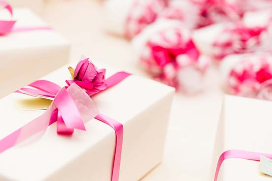 Gifts wrapped in white paper and pink ribbons