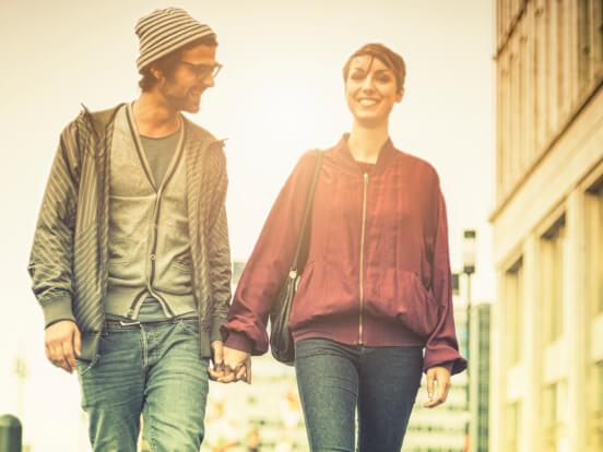 Un hombre y una mujer tomados de la mano en un paisaje de ciudad