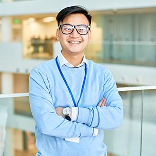 Hombre con gafas y jersey azul claro, brazos cruzados de perfil