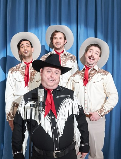 Group of singing a capella cowboys performing in front of a blue curtain.