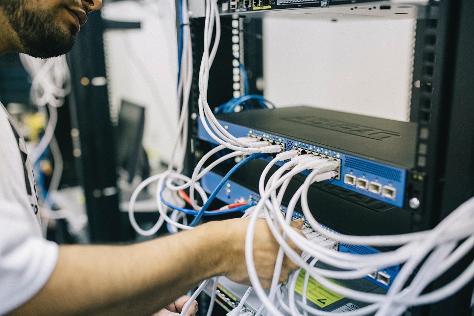 Technician inserting cables into a rack of servers