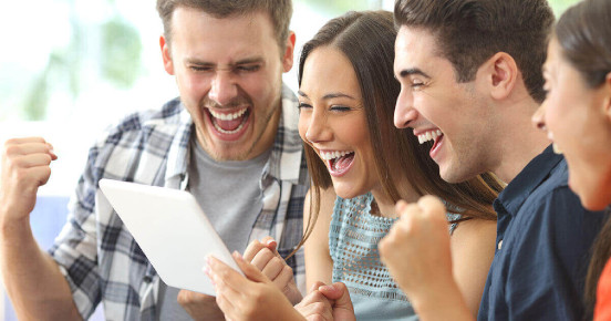 Group of people smiling whilst looking at a tablet screen