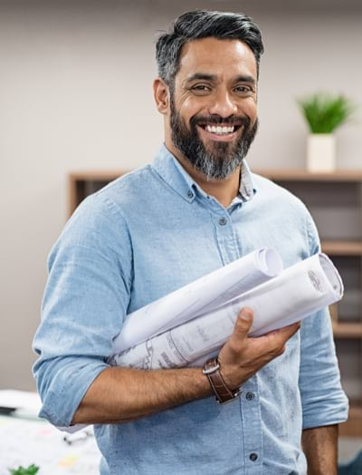 A smiling man holding blueprints, looking at the camera