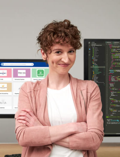 Coder standing in front of computer screens and smiling with her arms crossed. The screens behind her are displaying code and the Partner Portal interface.