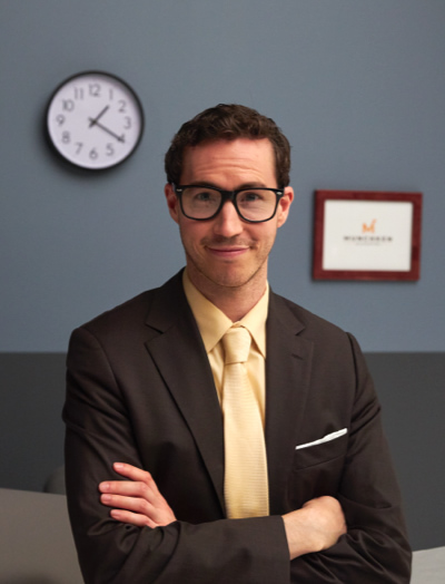 Smiling accountant with glasses standing with his arms crossed in his office.