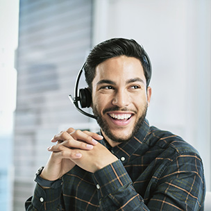 A man wearing a headset and laughing while looking off to the side